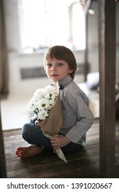 A boy with a bouquet of flowers in craft paper, a bouquet of chrysanthemums for mom and grandmother. Mother's Day Concept and Greetings.