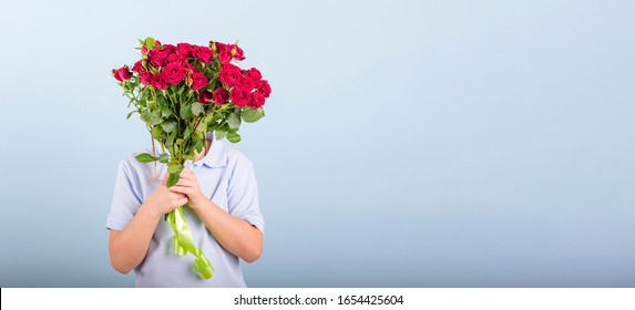 boy with a bouquet of red roses, portrait of a cute boy in a blue polo on blue background, greeting and gift for Mother's day or Valentine's day, banner