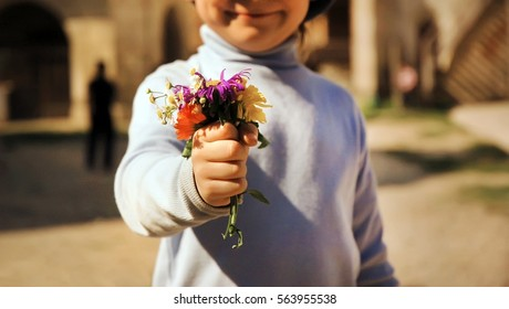 Boy with bouquet of wild flowers in a hand