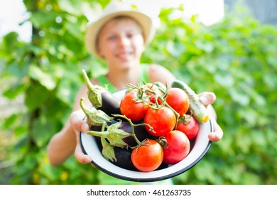A boy with a bowl of vegetables in the garden