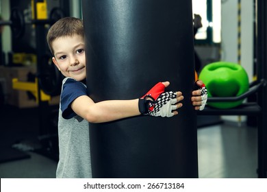Boy - box, fitness, sport. Young boy standing by bag boxing. The boy has been in the gym for boxing. Young man in a sports hall near the bag for boxing. Simulator. Trainer.