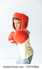 boy in boxing gloves and helmet fighting and looking at camera on white