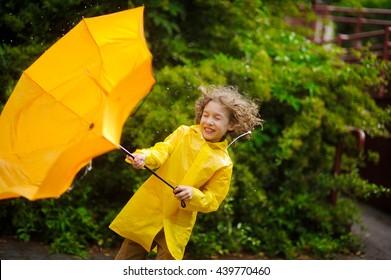 Der Junge in einem hellgelben Regenmantel mit Anstrengung hält einen Regenschirm vor Wind. Starker Wind zieht einen gelben Regenschirm aus den Händen. Der Wind hat zerrissene Haare, Tropfen eines Regentropfens auf den Kopf.