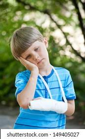 boy with a broken arm in park