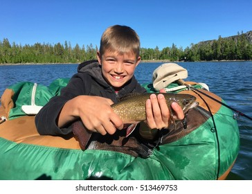 Boy with a Brook Trout caught fly fishing on a lake in the wilderness