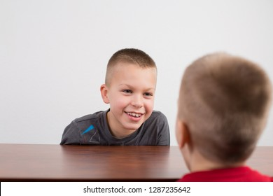 Boy brothers talking sitting at the desk, looking at each other.