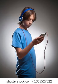 Boy with Brown Hair Listening to Music in Headphones.
