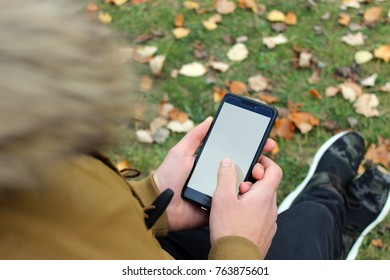 Boy in brown jacket looking at a smartphone