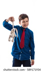 Boy brunette in a blue shirt with a red tie and a soft toy in hand on white background in studio