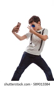 Boy brunette in a white shirt with suspenders and sunglasses makes selfie phone on a white background