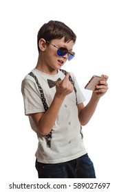 Boy brunette in a white shirt with suspenders and sunglasses playing on the phone on a white background