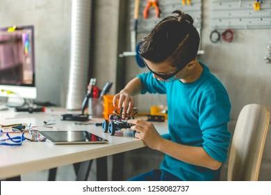 Boy building robotic car