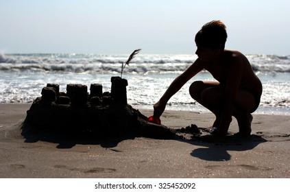 Boy building sand castle on the beach