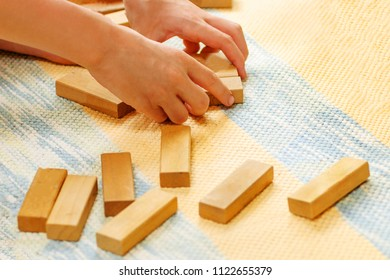 A boy builds from wooden cubes on a carpet
