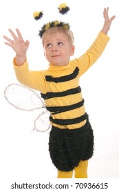 boy in bumble bee costume smelling red flower