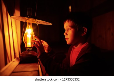 boy with a burning candle in his hands. the child touches an antique lamp