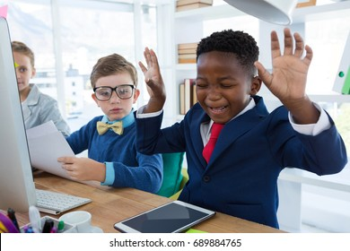 Boy as business executive laughing while looking at digital tablet in office