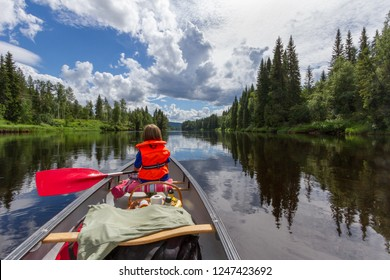 A boy canoe paddling on a calm river with the surrounding forest and cloudy sky reflecting in the the water in beautiful northern Sweden