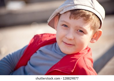 boy in a cap and a red waistcoat