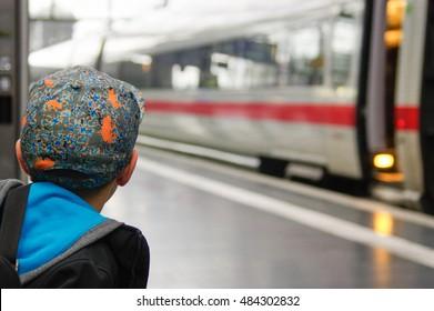 boy with a cap waits for train on railway platform
