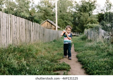 boy carries a piece of wood on his shoulder