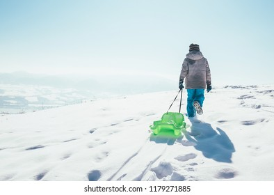 Boy carries the sled up on the snowy hill and enjoying the winter sledding time
