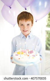 boy carrying birthday cake