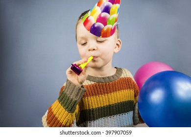 boy in a celebratory cap holding colorful balloons