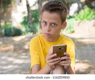 boy with cellphone in the park