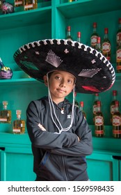 boy with charro hat and green tequila bottles background