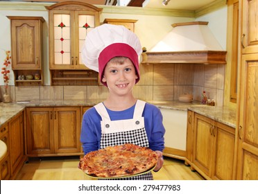 boy chef with pizza in kitchen