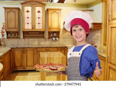 boy chef with pizza and thumb up in kitchen