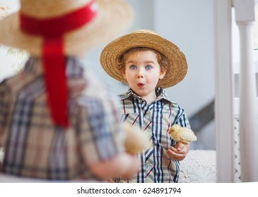 A boy and a chicken, a blond boy holding a yellow chicken in his hands and looking in the mirror, a boy and a bird, best friends, chick and kid.