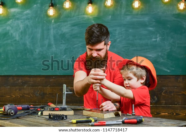 Boy, child busy in protective helmet learning to use screwdriver with dad. Teamwork in workshop concept. Father, parent with beard teaching little son to use tool screwdriver.