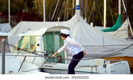 Boy child in captain's cap on a bridge near yachts.