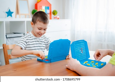 Boy child with dad playing warships and submarines are placed on the playing field in the game battleship. entertainment Board games at home in self-isolation in quarantine. Sea battle