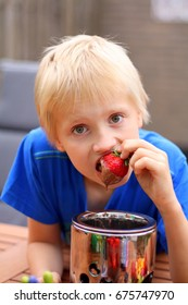 Boy, child eating strawberries in chocolate