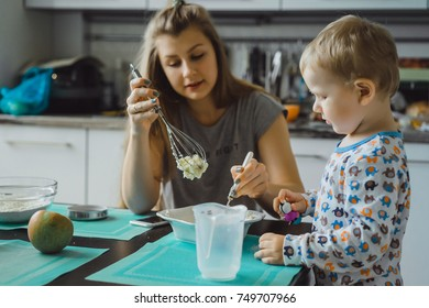 boy child in pajamas in the morning with mom cooking apple pie in the kitchen and playing with toys