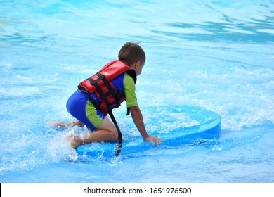 The boy child in the pool in the summer. The child in the water Park having fun. Happy holidays in the tropics. Child summer water attrazione.
