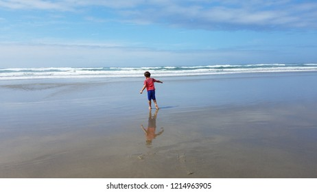 boy child with red shirt and blue shorts playing in sand and water at beach