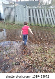 boy child with red shirt and blue pants walking in puddle