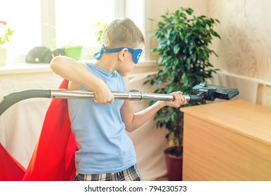 Boy child superhero costume playing is cleaning the house. The concept of children helping their parents in the form of a game