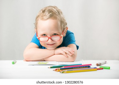 Boy child wears glasses, sits at the table and draws with pencils.