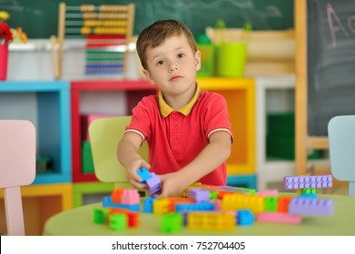 A boy in the children's room playing at the table.