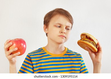 Boy chooses between fastfood and fruit on a white background