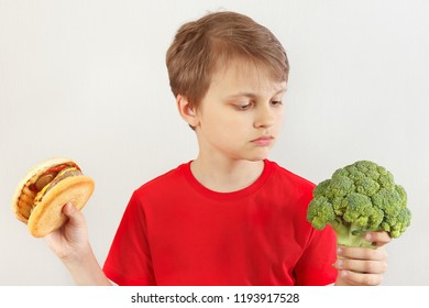 Boy chooses between hamburger and fresh broccoli on a white background
