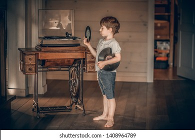 A boy is choosing a vinyl record for an old gramophone. Image with selective focus and toning