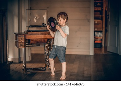 A boy is choosing a vinyl record for an old gramophone. Image with selective focus and toning.