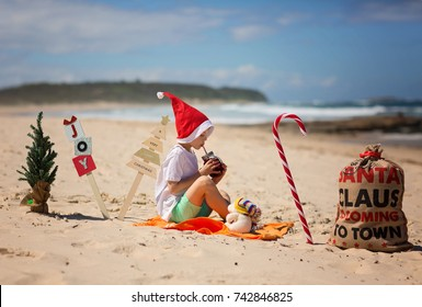Boy in christmas cap is sitting on the beach, ocean in background. Christmas on the beach