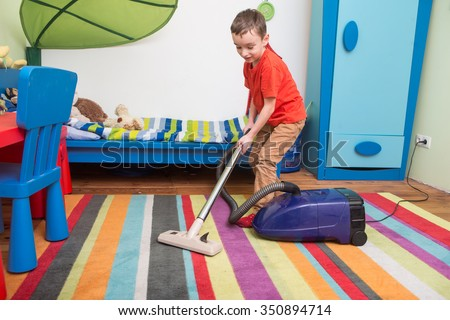 boy cleaning  floor with hoover